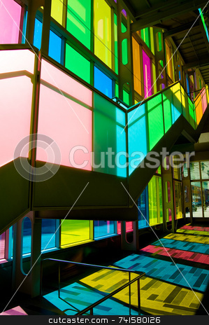 Colorful stairs stock photo, Stair lit by sunlight passing through tinted windows by Jean Larue-Frechette