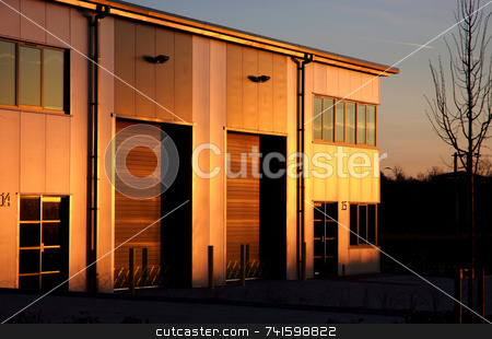Warm Glow stock photo, Sun setting and lighting up the side of a modern industrial unit in yellow by Paul Phillips