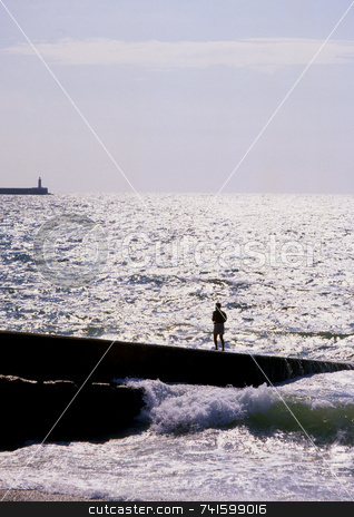 Silhouette at sea stock photo, Man standing on seaside breakwater during rough seas by Paul Phillips
