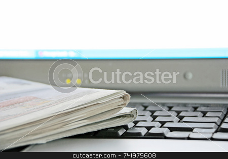 Newspaper and Computer stock photo, A newspaper on the keyboard of a laptop computer (focus is on the corner of the newspaper) by Georgios Alexandris