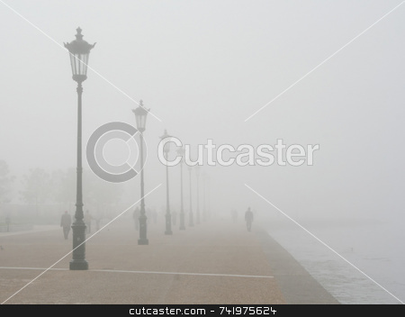 Foggy Seafront stock photo, A foggy pedestrian pavement on a seafront, with people taking a walk by Georgios Alexandris