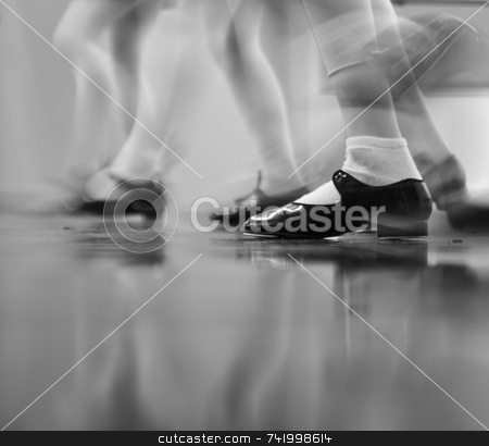 Tap Dance Class in Motion stock photo, Young dancers are learning - this group is vigorously tapping with tap shoes. Lots of motion - Black and white view by Mitch Aunger
