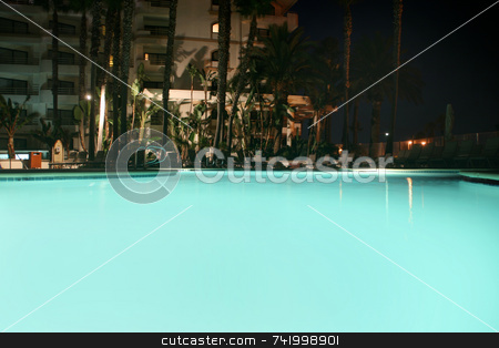 Evening at the hotel pool stock photo, The pool at a hotel lit up at night... plenty of copyspace by Mitch Aunger