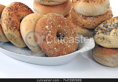 Bagels stock photo, Assorted bagels in dish and stacked in background by Jack Schiffer