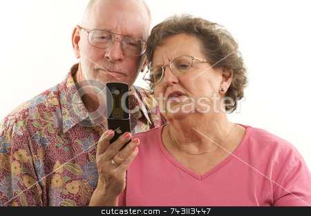 Senior Couple and Cell Phone stock photo, Senior Couple looks at the screen of a cell phone. by Andy Dean
