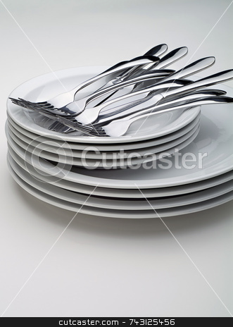 Silverware on a stack on white plates stock photo, Silverware on a stack on white plates on a white background, vertical by Vince Clements