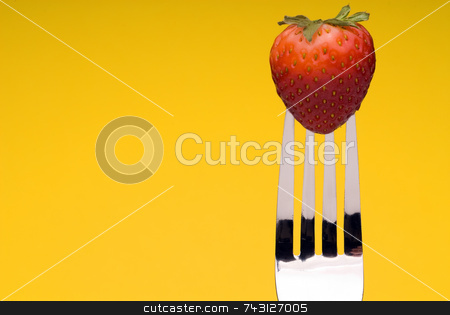Strawberry on Fork - yellow background stock photo, A fresh red strawberry on a fork against a graphic yellow background by Vince Clements