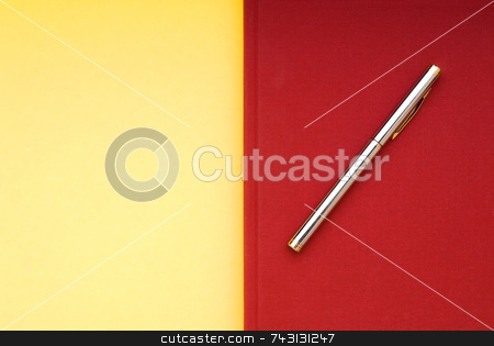 Red book on a yellow background stock photo, A stricking image of a silver pen on a bright red book on a yellow background by Vince Clements