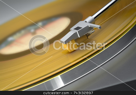 Yellow vinyl record on turntable - tilted view stock photo, Tilted close up of headshell and stylus on a turntable with yellow vinyl record by Vince Clements