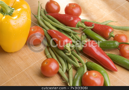 Sunlit vegetables stock photo, A group of fresh sunlit vegetables on a wooden cutting board by Vince Clements