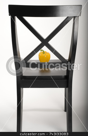 Black chair and pepper stock photo, Artisitic black wooden chair with a bright yellow pepper framed in the chair back. Light is fading off to the right. by Vince Clements