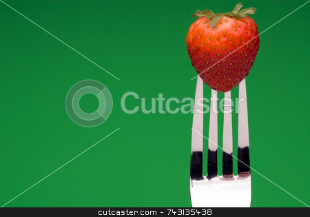 Strawberry on Fork - green background stock photo, A fresh red strawberry on a fork against a graphic green background by Vince Clements