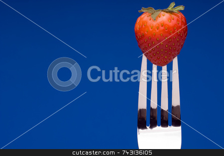Strawberry on Fork - blue background stock photo, A fresh red strawberry on a fork against a graphic blue background by Vince Clements