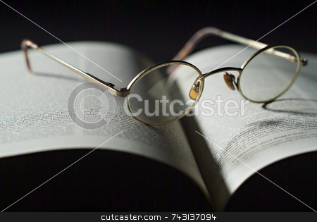 Book and reading glasses stock photo, Closeup of reading glasses on large book by Vince Clements