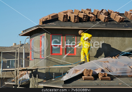 Construction Worker Pressure Washes  stock photo, Construction worker pressure washes fresh applied surface of new home exterior. by Andy Dean