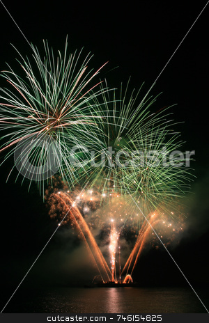 Green and orange fireworks stock photo, Bright green and orange fireworks against the dark sky by Jonas Marcos San Luis