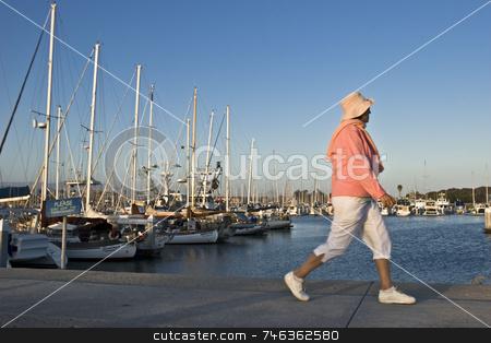 Ventura Harbor stock photo, A woman walking down the sidewalk  at the Ventura Harbor. by Brett Benham
