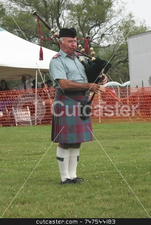 A Scot Playing Pipes stock photo, A piper playing with his band in a circle, competing against other pipe bands for honours. This piper is wearing the Ancient Lindsay tartan. by Ray Carpenter