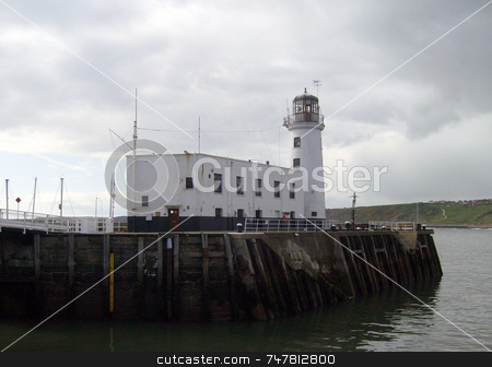 White lighthouse stock photo, White lighthouse at harbor mouth by Martin Crowdy