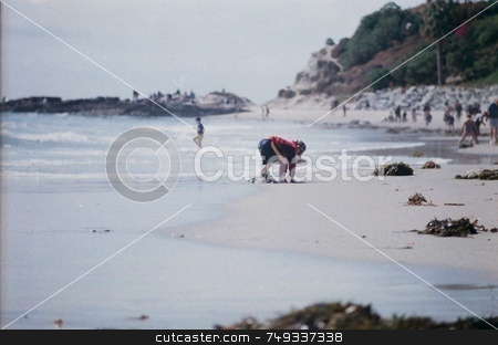 Boy digging on a sandy beach stock photo, A boy digging in the sand at the beach by Rob Wright