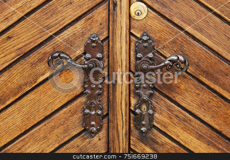 Main entrance stock photo, Double iron handle on a wooden door by Massimiliano Leban