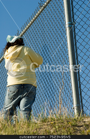 Trapped stock photo, A low angle view of a young girl standing by a chain fence by Richard Nelson