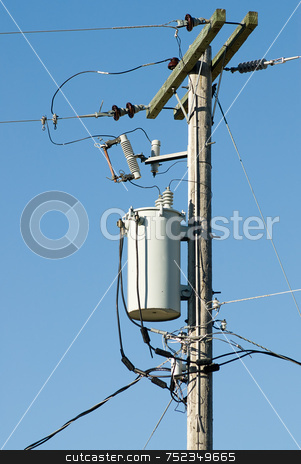 Powerline Transformer stock photo, A transformer on a powerline pole shot against a blue sky by Richard Nelson