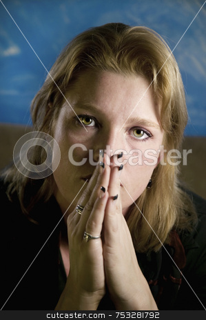 Blonde Woman with Folded Hands stock photo, Portrait of a blonde woman with her hands folded in front of her face. by Scott Griessel