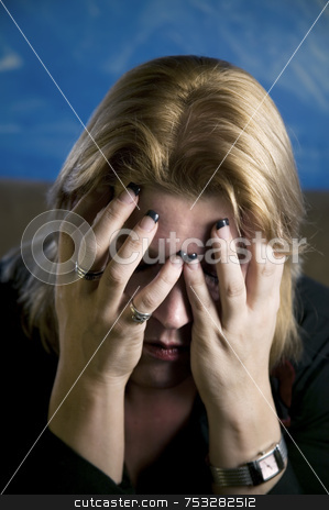 Blonde Woman in Despair stock photo, Close up of blonde woman in a studio setting hiding her face in her hands. by Scott Griessel