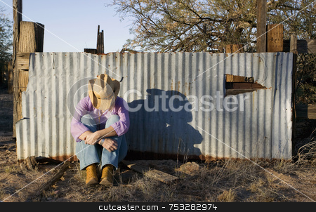 Woman in a Cowboy Hat with her Head Down stock photo, Woman wearing a straw cowboy hat with her head down leaning against a corrugated metal fence. by Scott Griessel