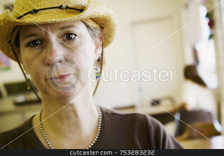 Woman in Cowboy Hat stock photo, Woman indoors in a cowboy hat looks intently at the camera. by Scott Griessel