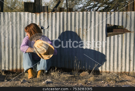 Woman in a Cowboy Hat Looking Right stock photo, Woman in a Cowboy hat sitting against a Corrugated Metal fence and Looking to her Right. by Scott Griessel