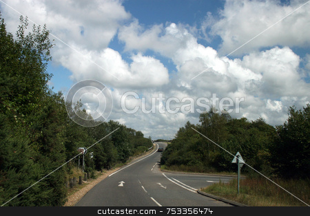 The road to nowhere stock photo, A road in the uk with fluffy clouds. by Lucy Clark