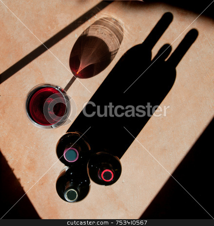 Wine Bottles and Wine Glass with Dramatic Shadow stock photo, Wine bottels and wine glass with heavy side-light and long, dramatic shadow. by Scott Griessel