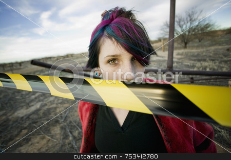 Punk Girl Behind Caution tape stock photo, Punk girl outdoors behind a strip of yellow and black caution tape by Scott Griessel
