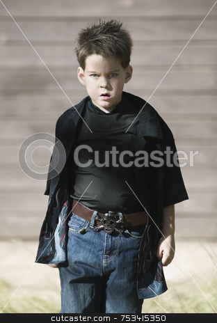 Boy with Attitude stock photo, Young boy with a defiant attitude wearing a black shirt and a pirate belt buckle. by Scott Griessel