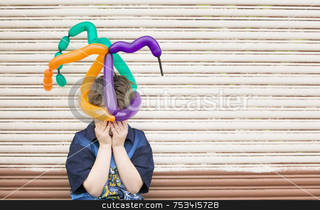 Sad Boy with a Balloon Hat stock photo, Young boy wearing a balloon hat hides his face by Scott Griessel