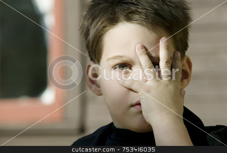 Boy with a hand in front of his face stock photo, Close up of a young boy with his hand covering one eye. by Scott Griessel