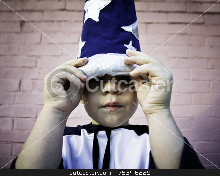 Boy looking out from a wizard hat stock photo, Young boy lifts the brim of a wizard hat and peers out. by Scott Griessel