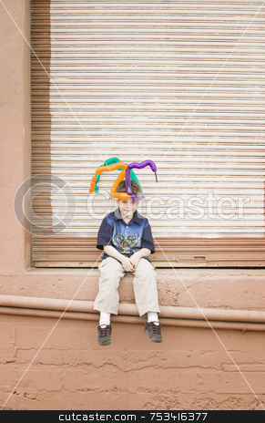 Boy with a Balloon Hat stock photo, Young boy wearing a balloon hat sitting on a ledge by Scott Griessel
