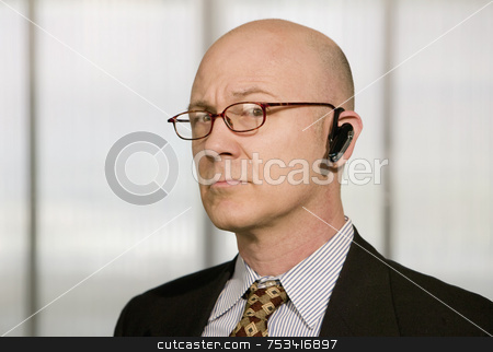 Businessman with a hands-free phone stock photo, Portrait of businessman with a hands-free phone in his ear by Scott Griessel