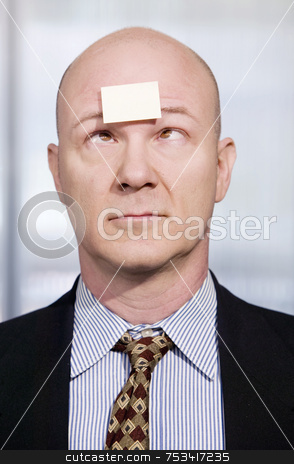 Businessman with a blank note on his forehead stock photo, Bald businessman in with a blank sticky note on his forehead by Scott Griessel