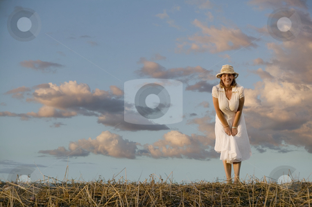 Woman Against a Cloudy Sky stock photo, Wide angle shot of a woman against a cloudy sky at dusk. by Scott Griessel