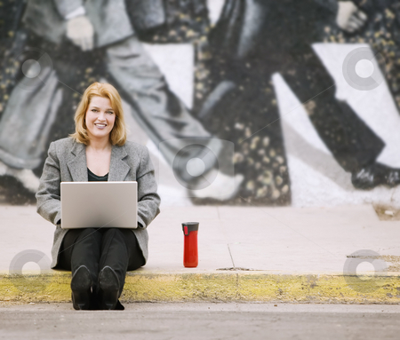 Woman with laptop on a sidewalk stock photo, Pretty smiling woman with a laptop computer sitting on the sidewalk by Scott Griessel