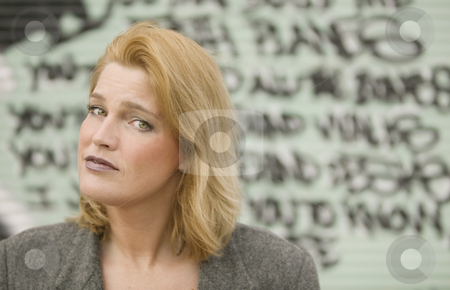Woman in front of graffiti stock photo, Portrait of a blonde woman in front of graffiti by Scott Griessel