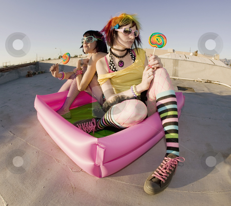Girsl on a roof in a plastic pool stock photo, Fisheye shot of girls in brightly colored clothing in a plastic pool on a roof with sunglasses and lollipops by Scott Griessel