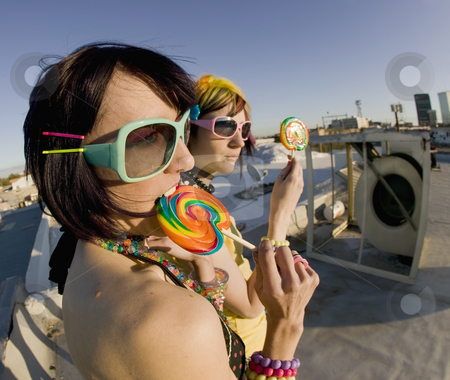 Fun girls on the roof with lollipops stock photo, Fisheye shot of girls in brightly colored clothing on a roof with sunglasses and lollipops by Scott Griessel