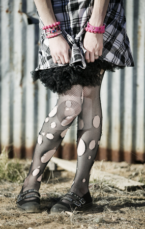 Stockings with Holes stock photo, Hem of a dress and woman's legs with ripped stockings by Scott Griessel