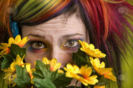 Punk woman with plastic flowers stock photo, Pretty young woman peeks out from behind plastic flowers. by Scott Griessel