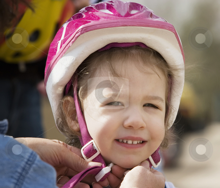 Little girl in a bicycle helmet stock photo, Young girl having a bicycle helmet snapped on her head smiles at the camera by Scott Griessel
